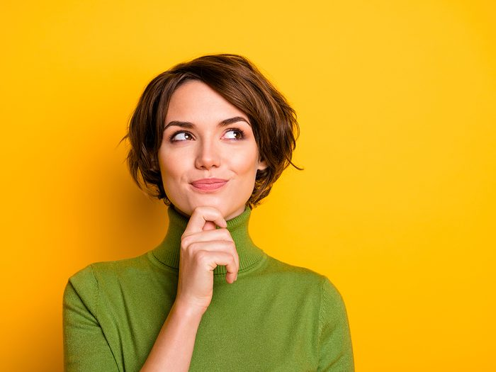 Smartest zodiac sign - Closeup photo of amazing short hairdo lady looking up empty space deep thinking creative person arm on chin wear casual green turtleneck isolated yellow color background