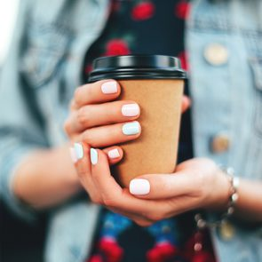 Woman holding paper cup of coffee take away
