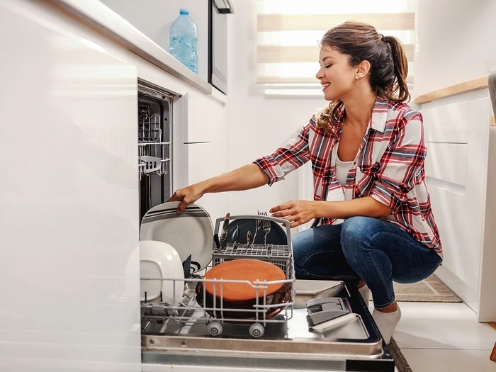 Tips from professional cleaners - Woman putting dishes into dishwasher
