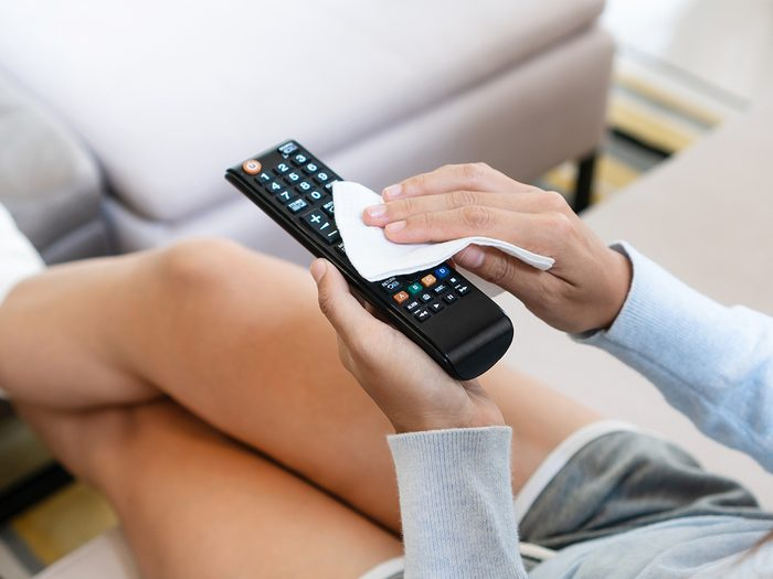 Tips from professional cleaners - woman hands cleaning the tv remote control with disinfectant wet wipes. Prevention of bacteria and covid-19 virus spreading concept.
