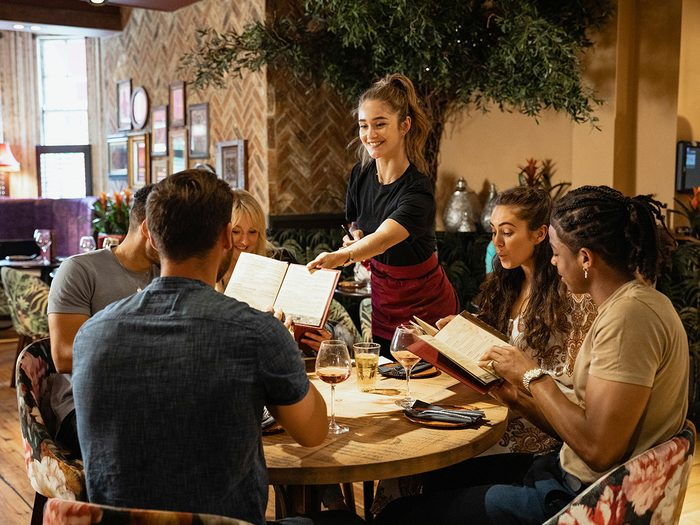 Brain exercises - group of friends looking at menus together in a restaurant, which have been given to them by a waitress.