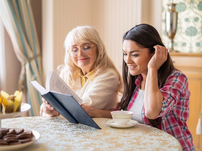 Elderly Mother Listens To Her Lovely Daughter Reading A Book Out Loud. Young Woman Tucks Her Hair Behind An Ear While Reading A Book To Her Mom.