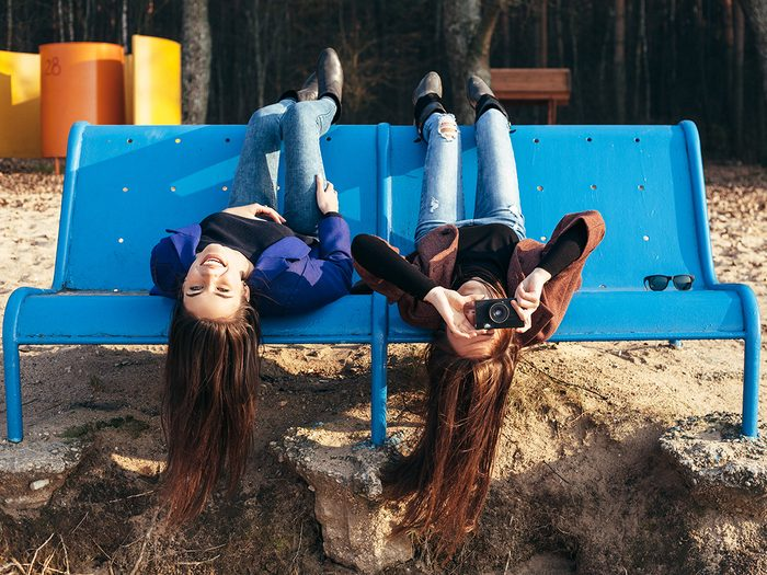 Brain exercises - Two funky friends making pictures lying upside down on a bench on the beach. Outdoor lifestyle portrait
