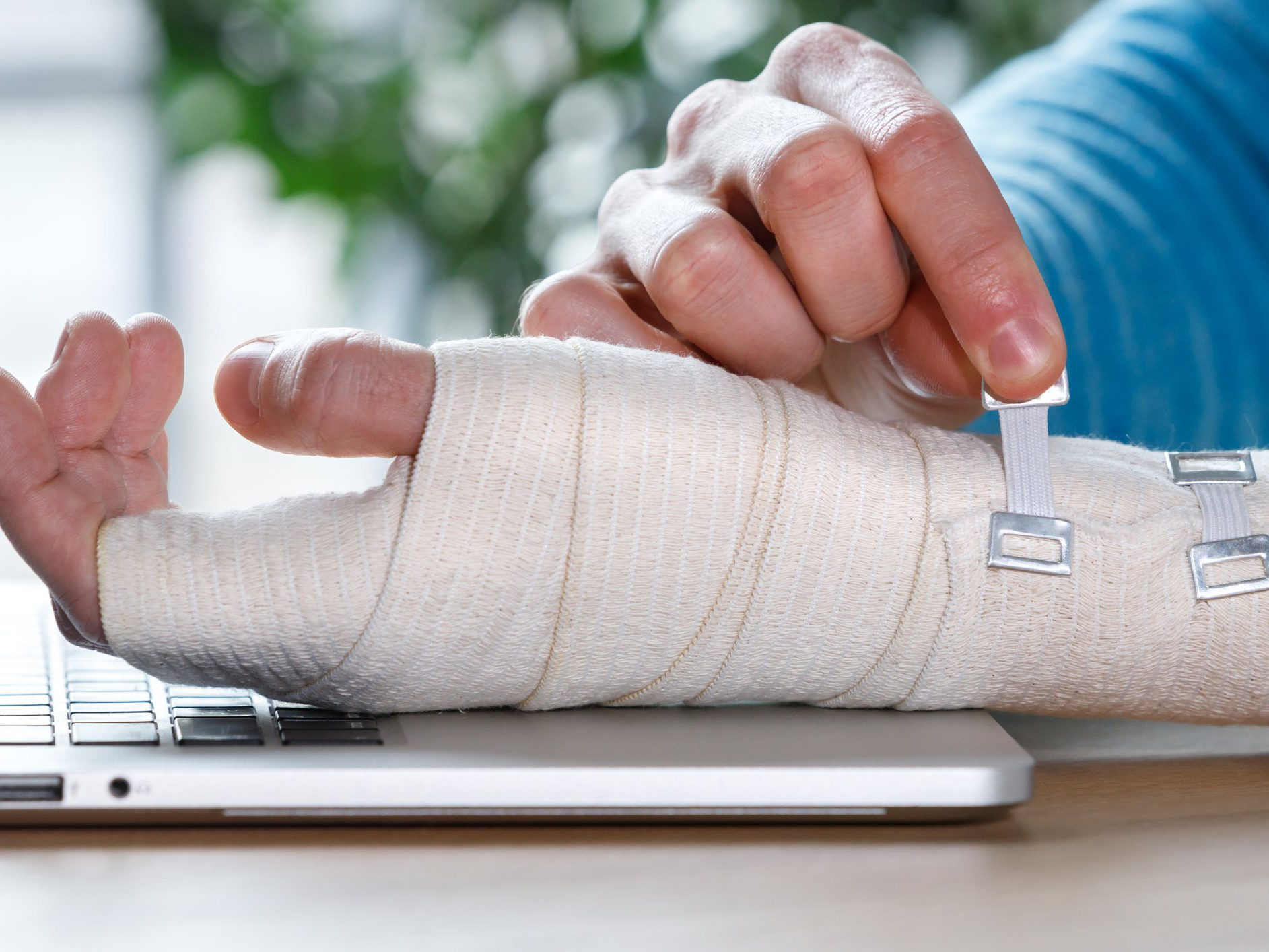 What you need to know about carpal tunnel syndrome - Close up of man arms wrapping his painful wrist with Flexible elastic supportive orthopedic bandage caused by prolonged work on laptop. Carpal tunnel syndrome, arthritis, arm sprain concept.