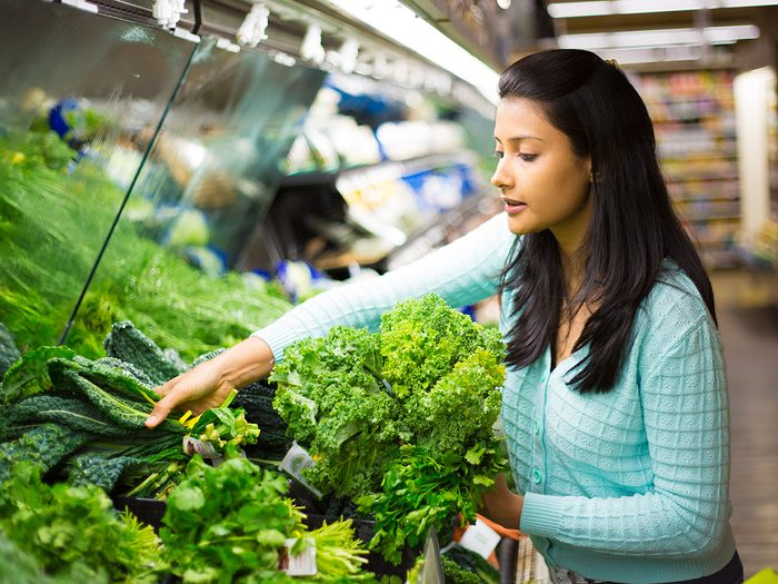 Foods that lower blood pressure - woman shopping for leafy greens