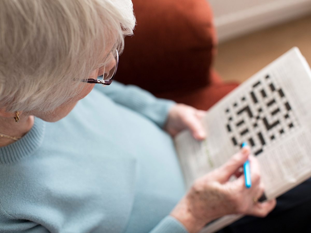 Morning brain exercises - woman doing crossword puzzle