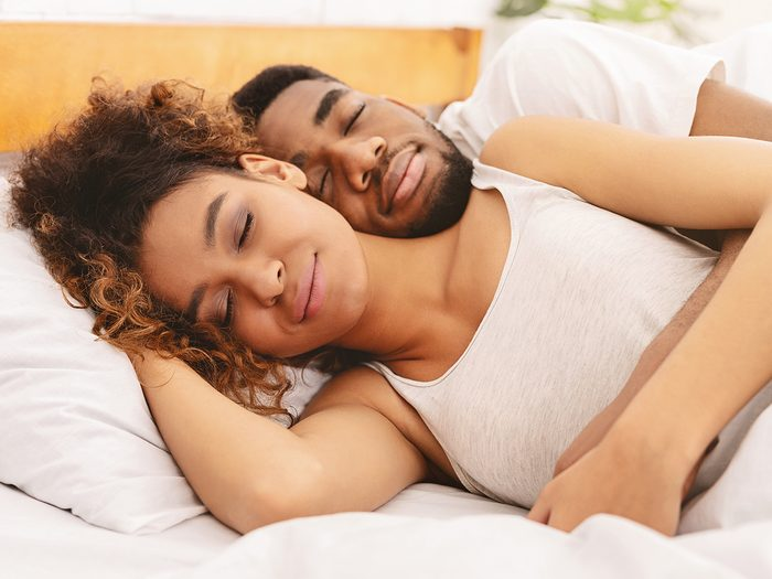 Secrets to a good night's sleep - couple cuddling in bed