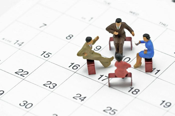 Miniature 4 people sitting on red staples placed on a white Calendar. meeting or Discussion using as background business concept with copy space and white space for your text or design.