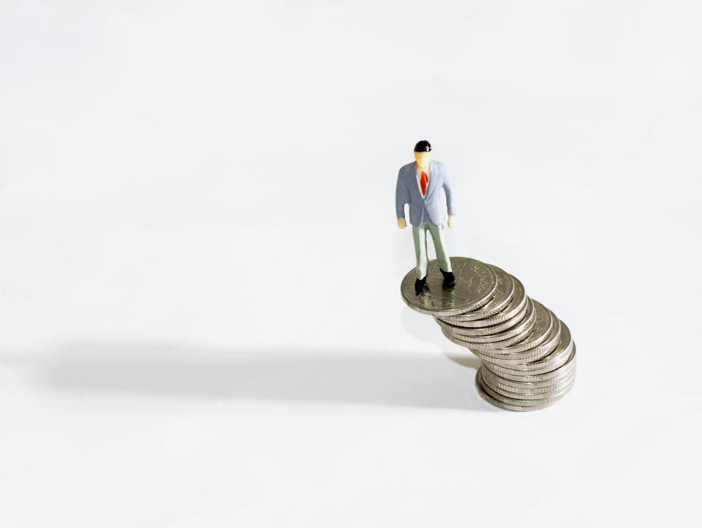 Financial stability with Business man Figure miniature or small people,shadow and money coin isolated on white background.Concept business.