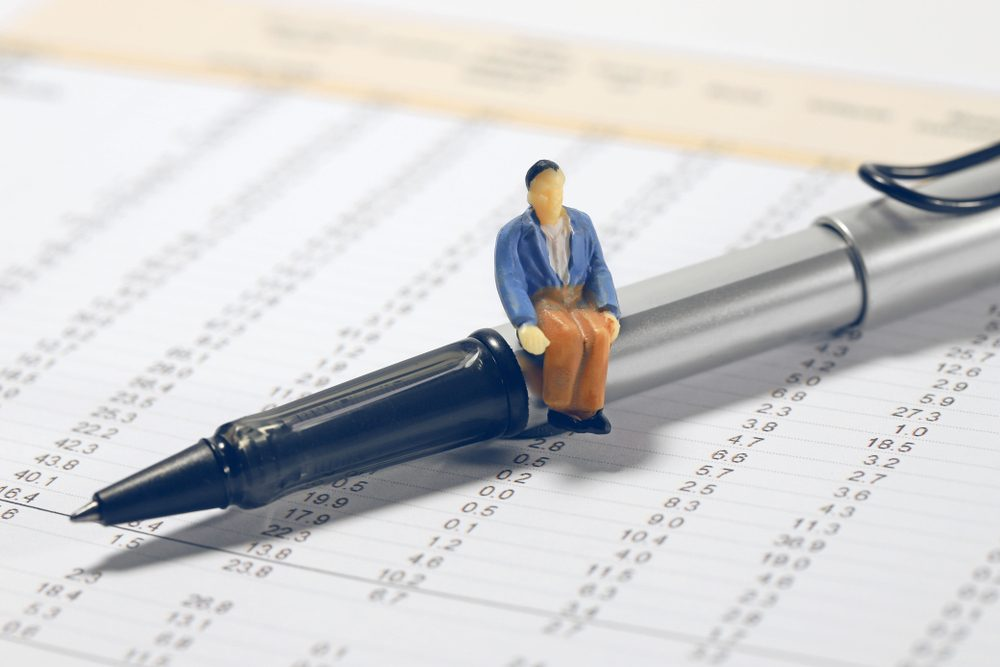 Successful business concept. Miniature businessman sitting and analysis on pen with financial statements background.
