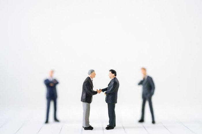 Miniature businessman handshake with success deal business using as background commitment, agreement, investment and partnership concept