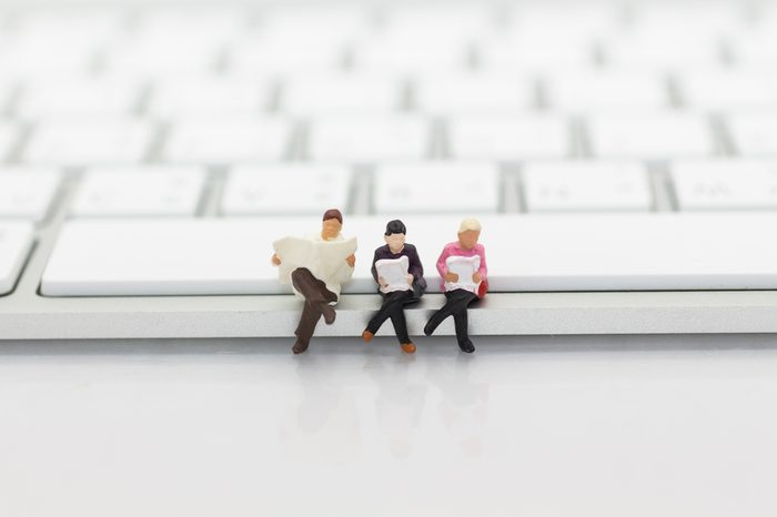 Miniature people sitting on keyboard using as background education or business concept.