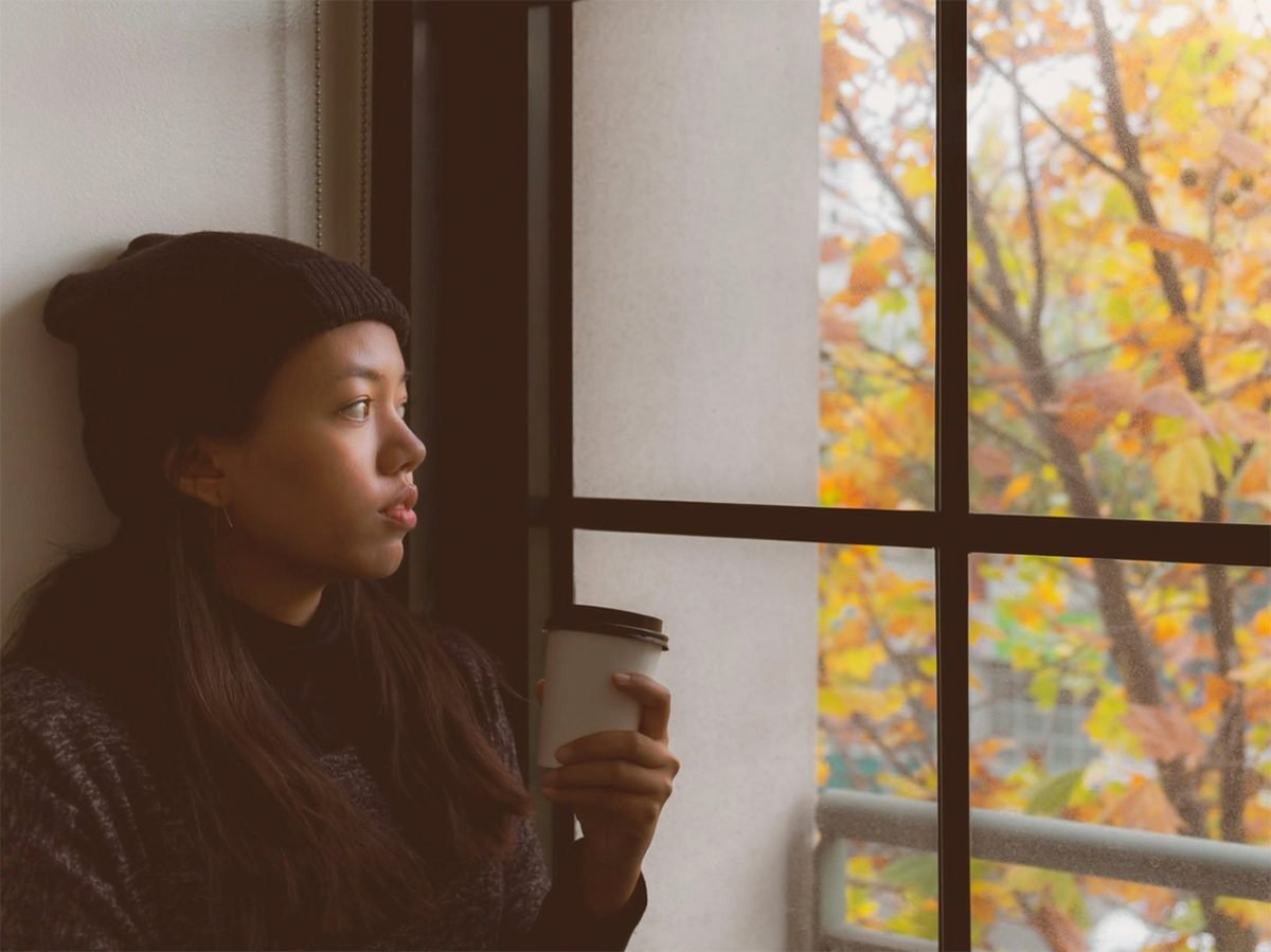 What is autumn anxiety? Young woman staring out of window in autumn