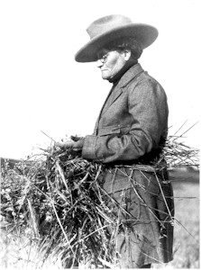 Agricultural journalist Ella Cora Hind handles a bale of straw.