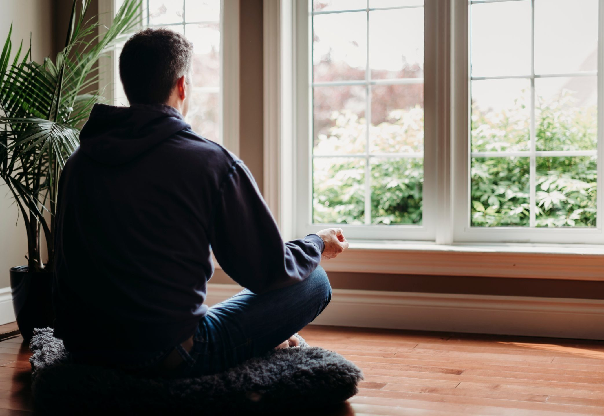 Man sitting on the floor indoors meditating in front of windows.