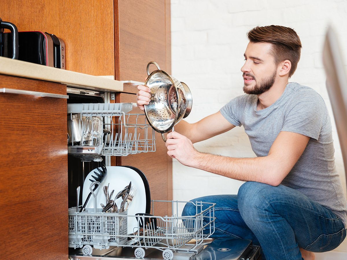 Bad cleaning habits - man loading dishwasher