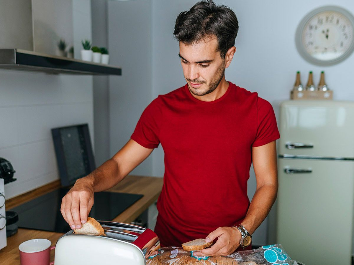 Common toaster mistakes - Man toasting bread with toaster in the kitchen