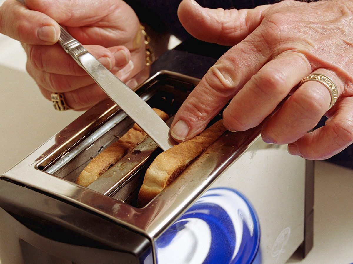 Common toaster mistakes - Senior man getting toast out of toaster with knife, close-up