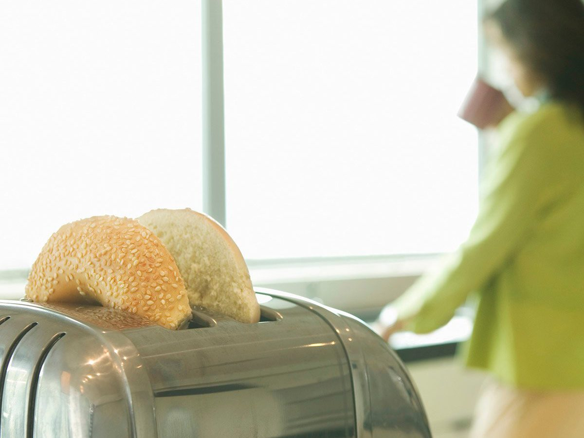Common toaster mistakes - Woman in kitchen drinking coffee, bagels in toaster (focus on toaster)