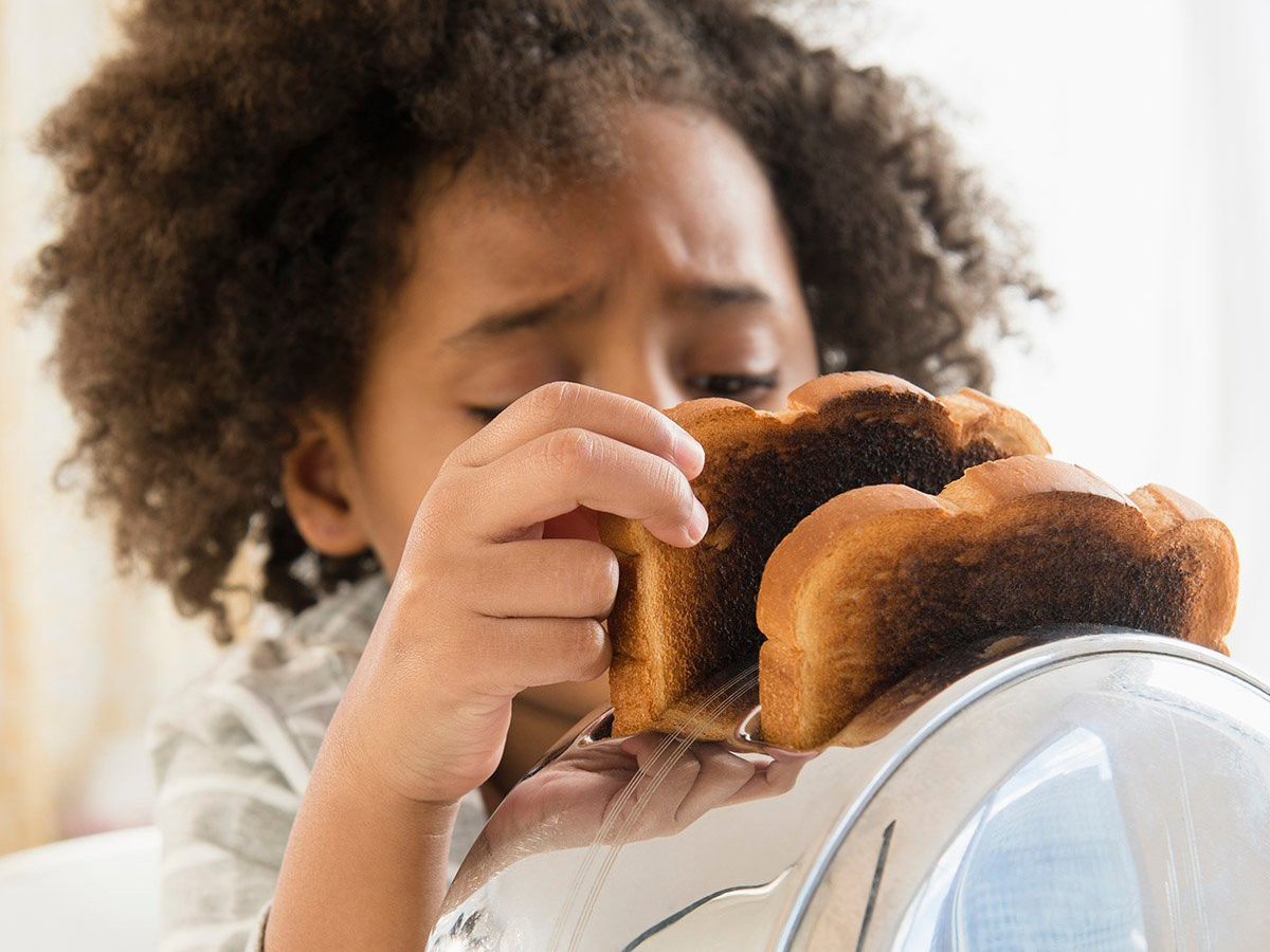 Common toaster mistakes you might be making - girl burning toast in toaster