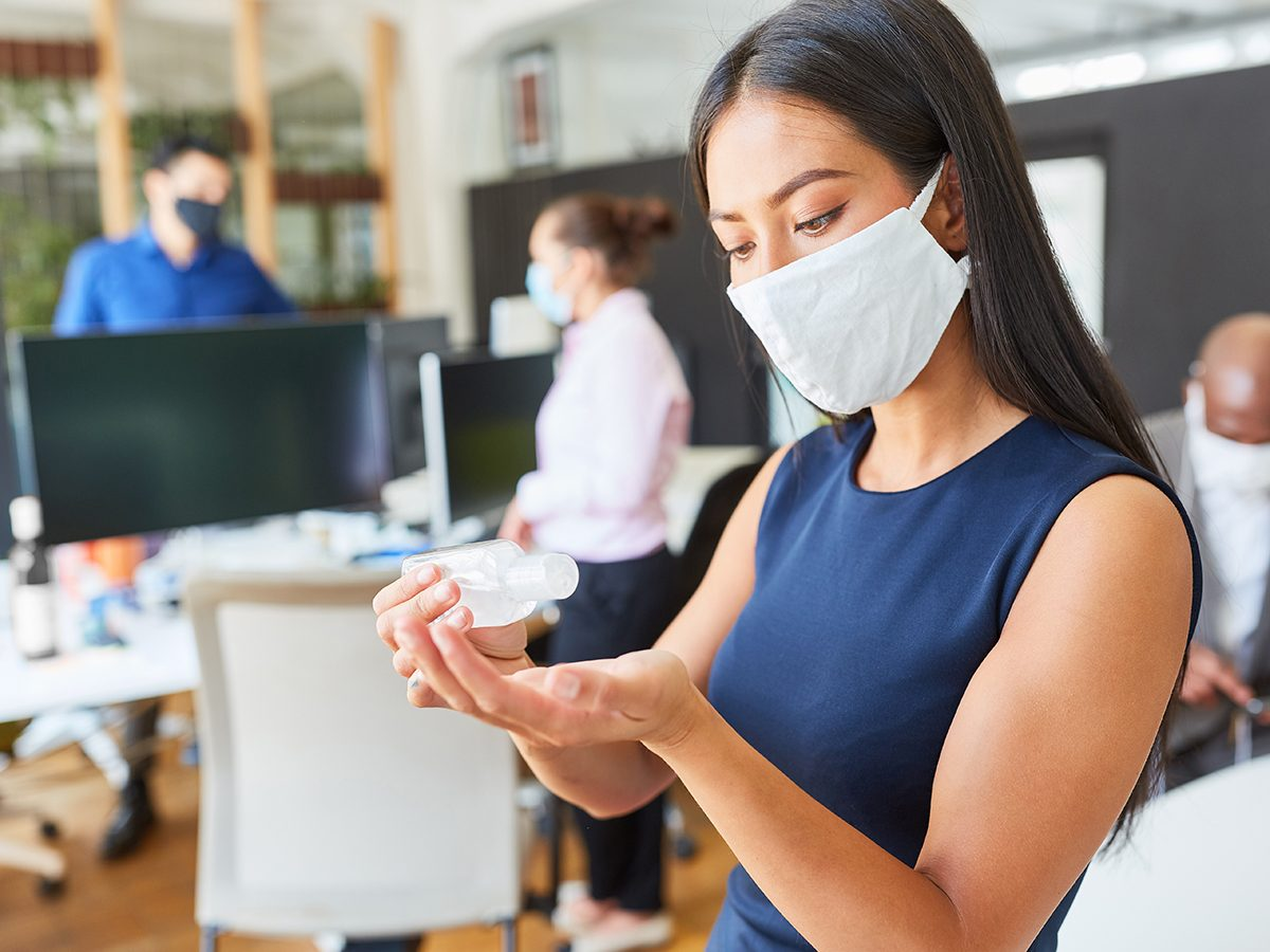 Most likely winter shortages due to COVID-19 - woman wearing mask and using hand sanitizer