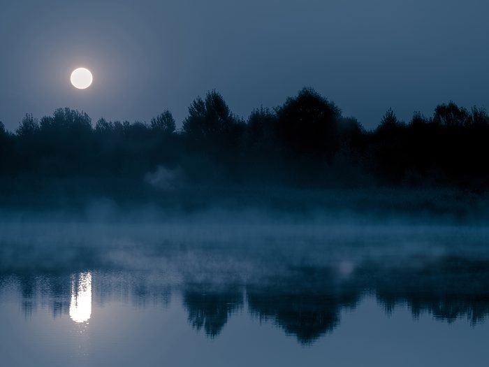 Creepy facts Canada - Night mystical scenery. Full moon over the foggy river and its reflection in the still water.