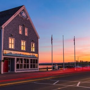 Day trips from Halifax - Hector Heritage Quay museum and flagpoles in sunset light with car tail light trails in the foreground.