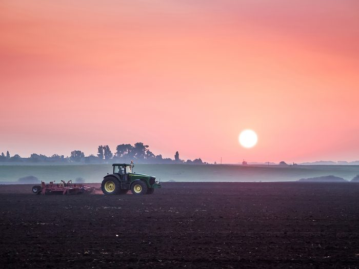 Daylight saving time myths - tractor in field at sunrise