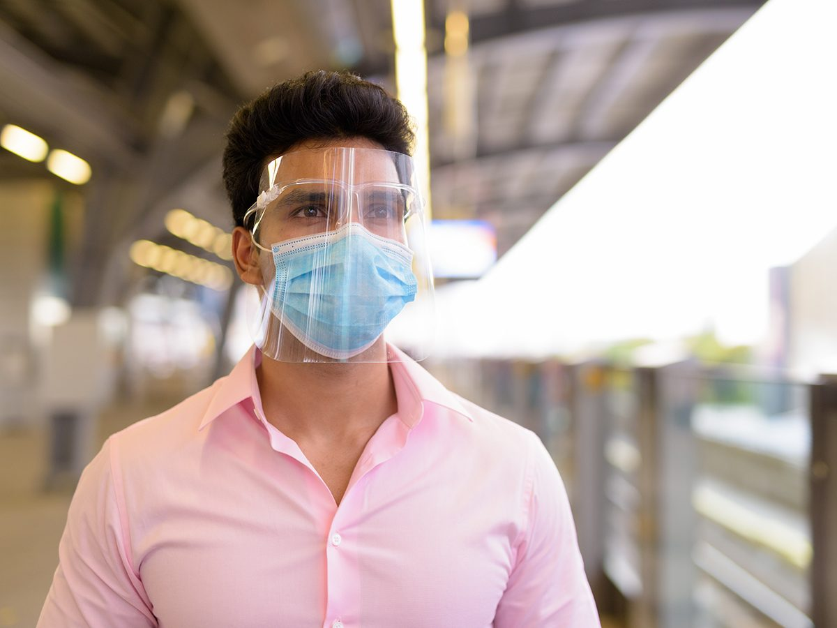 Do face shields really stop coronavirus - man wearing mask and face shield at train station