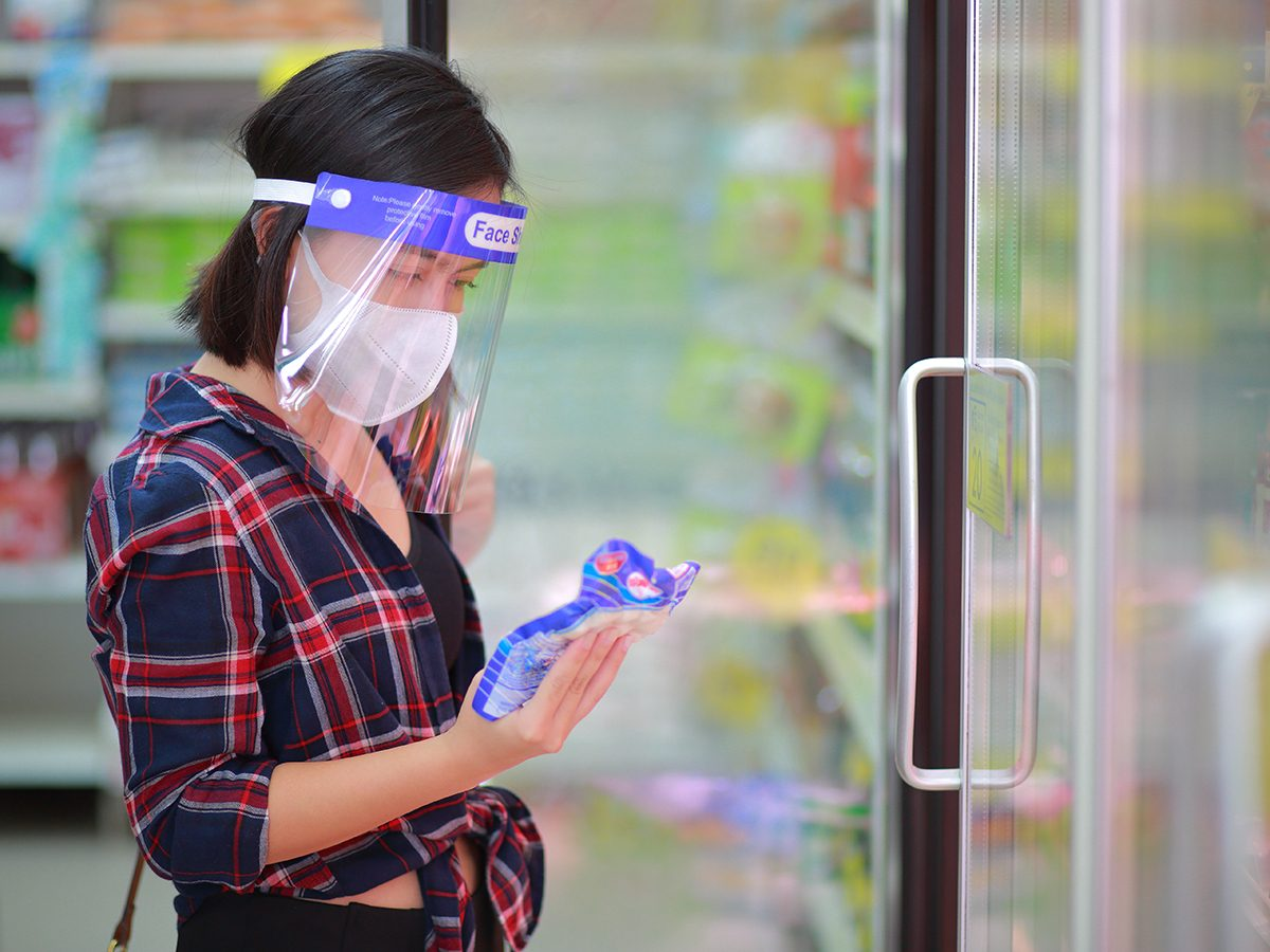 Do face shields really stop coronavirus - woman wearing mask and face shield at grocery store