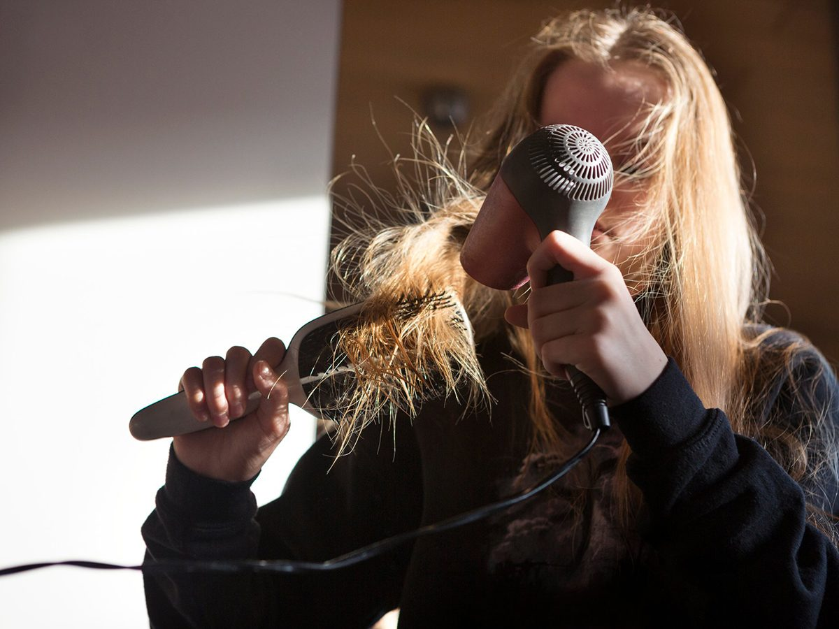 Home fire hazards - Girl (12-13) blow drying her long hair with an electric hairdryer in a bedroom