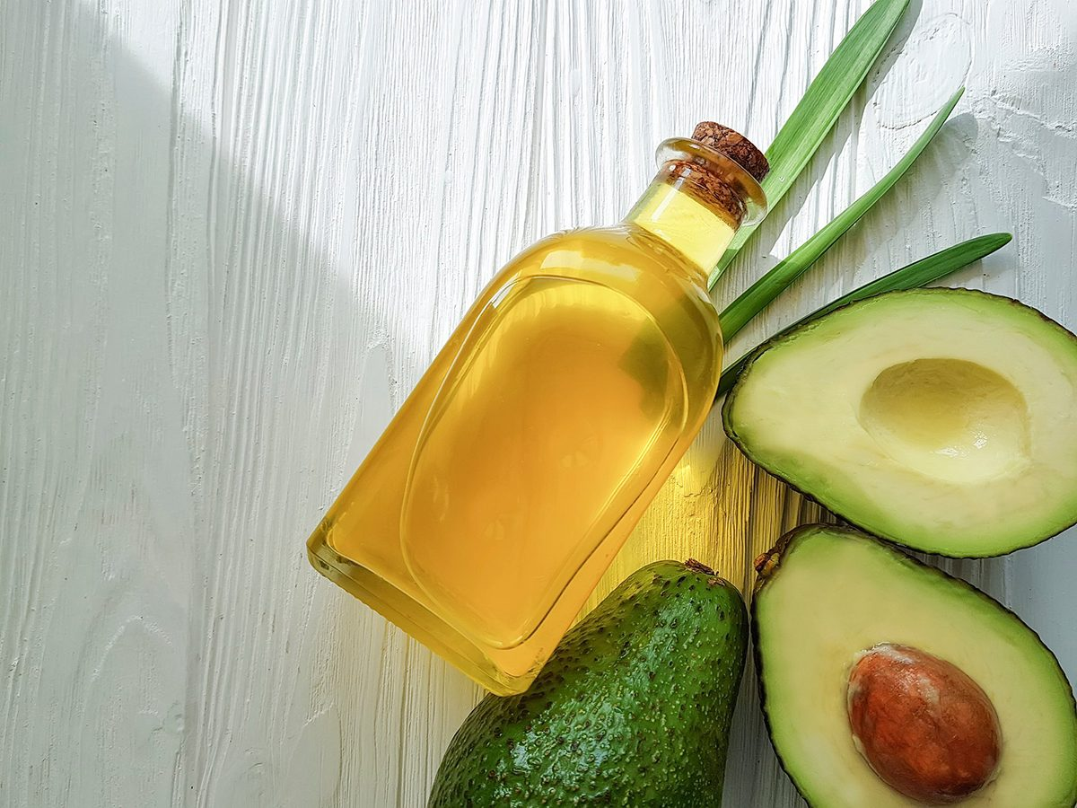 Healthiest cooking oil - avocado oil on white wooden