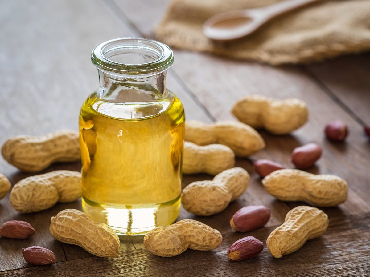 Healthiest cooking oil - Peanut oil in glass bottle and peanuts on wooden table