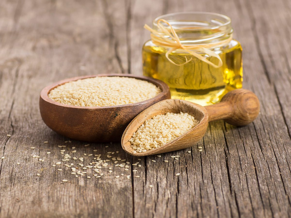 Healthiest cooking oil - Glass bottle of sesame oil and raw sesame seeds in wooden shovel with burlap sack on wooden table. Uncooked sesame background concept with copy space