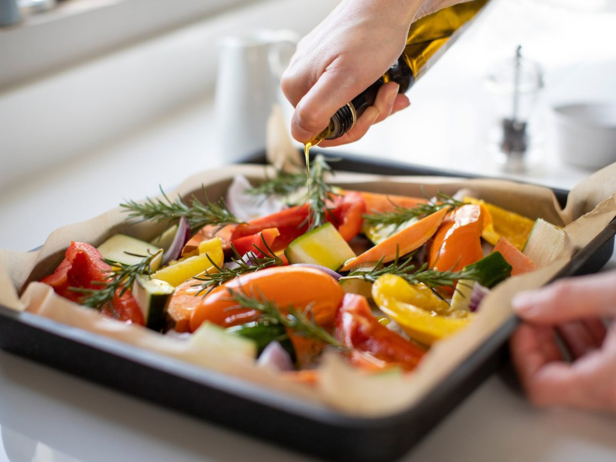 Healthiest cooking oil - Close Up Of Seasoning Tray Of Vegetables For Roasting With Olive Oil Ready For Vegan Meal