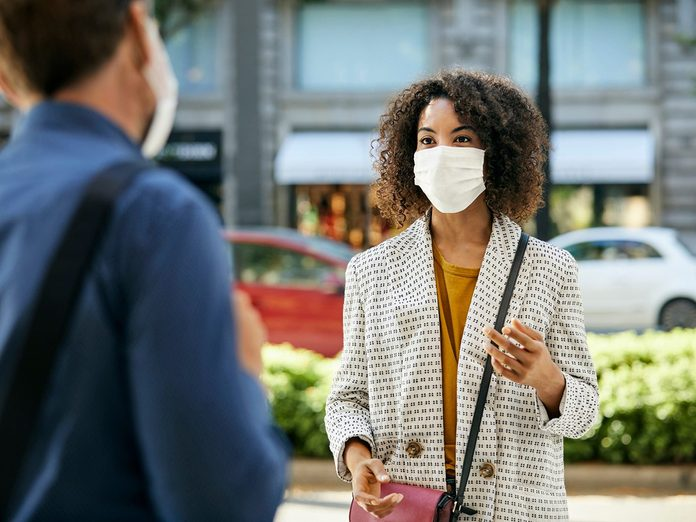 How to read people's face when they're wearing a mask - Businesswoman discussing with coworker in city. Female entrepreneur talking to male colleague during pandemic. They are maintaining social distance