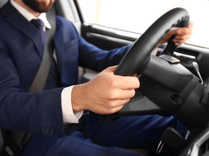 How to reduce car insurance - man in suit driving safely
