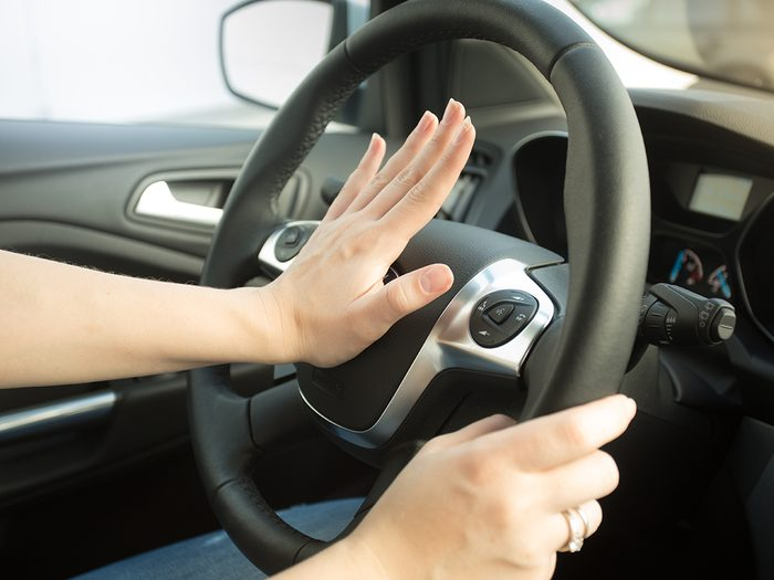 How to reduce car insurance - woman honking car horn