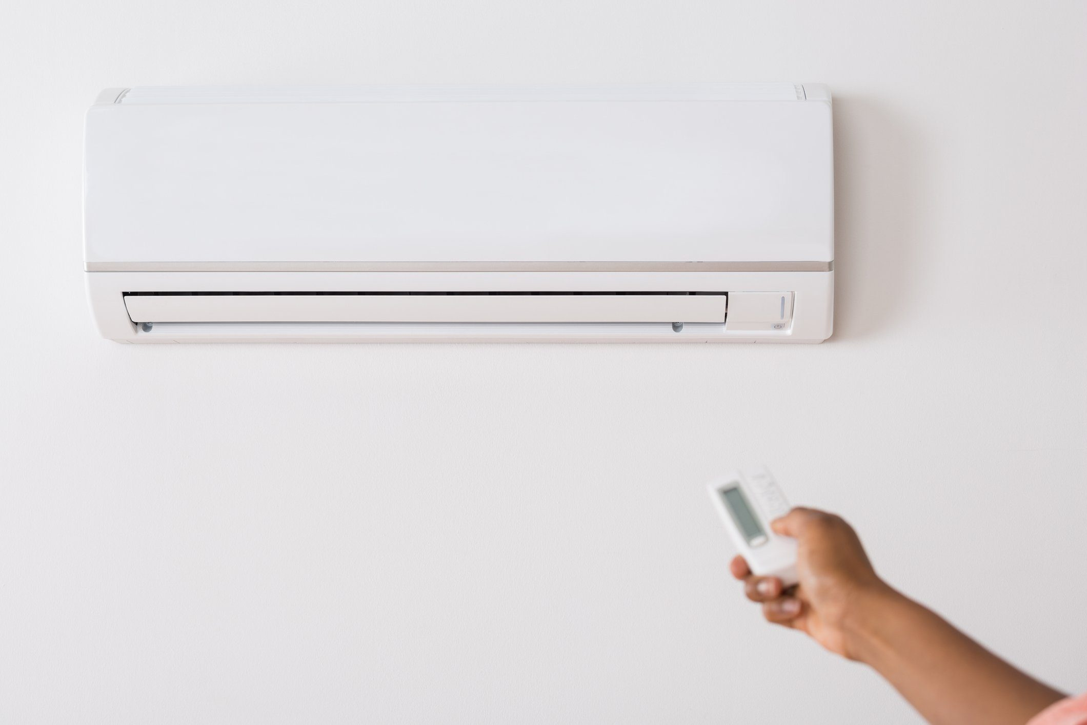 Person's Hand Holding Remote To Operate Air Conditioner