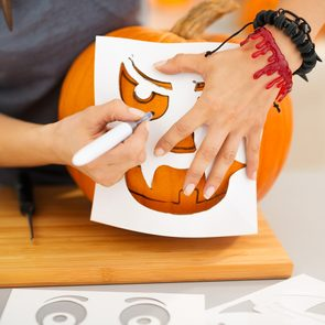 Pumpkin carving templates - Closeup on woman using stencils to carve big orange pumpkin Jack-O-Lantern for Halloween party. Traditional autumn holiday