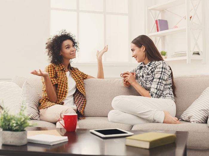 Rude conversation habits - Two happy young female friends with coffee cups conversing in living room at home, chatting about their life and relations, gossip and slumber party concept, copy space