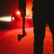 Scary things that happened in real life - maniac killer near the car at night close-up. silhouette of a man with an ax in his hand at night in a fog