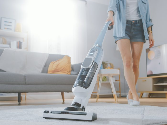 Vacuum cleaner - Woman vacuuming living room carpet