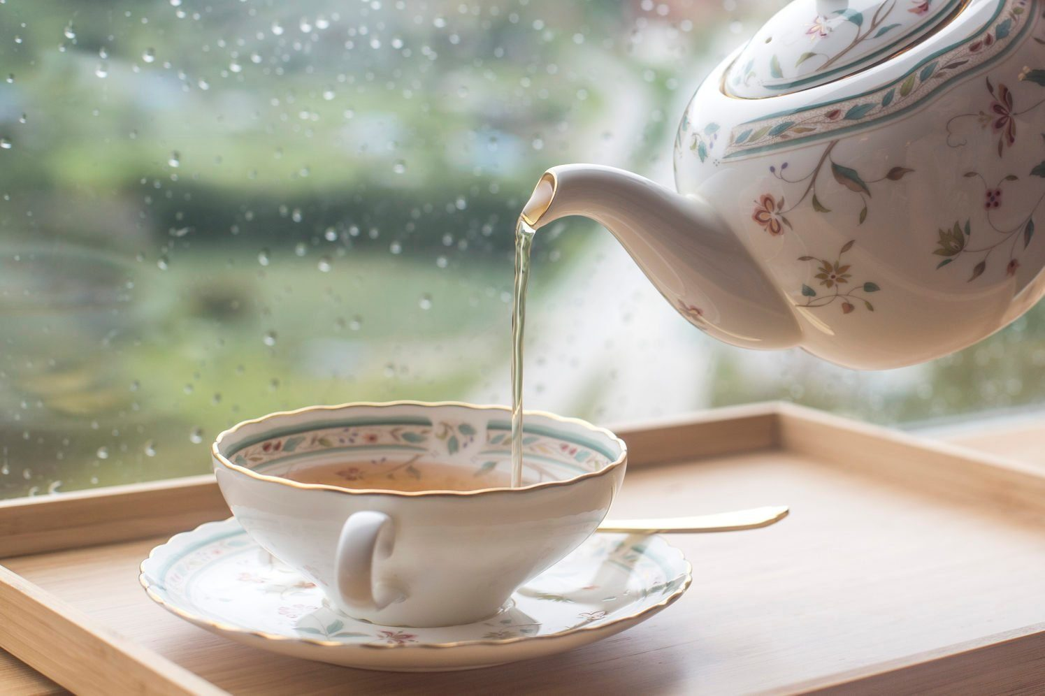 A man pouring black tea from the ceramic teapot in cafe. Close up on hands