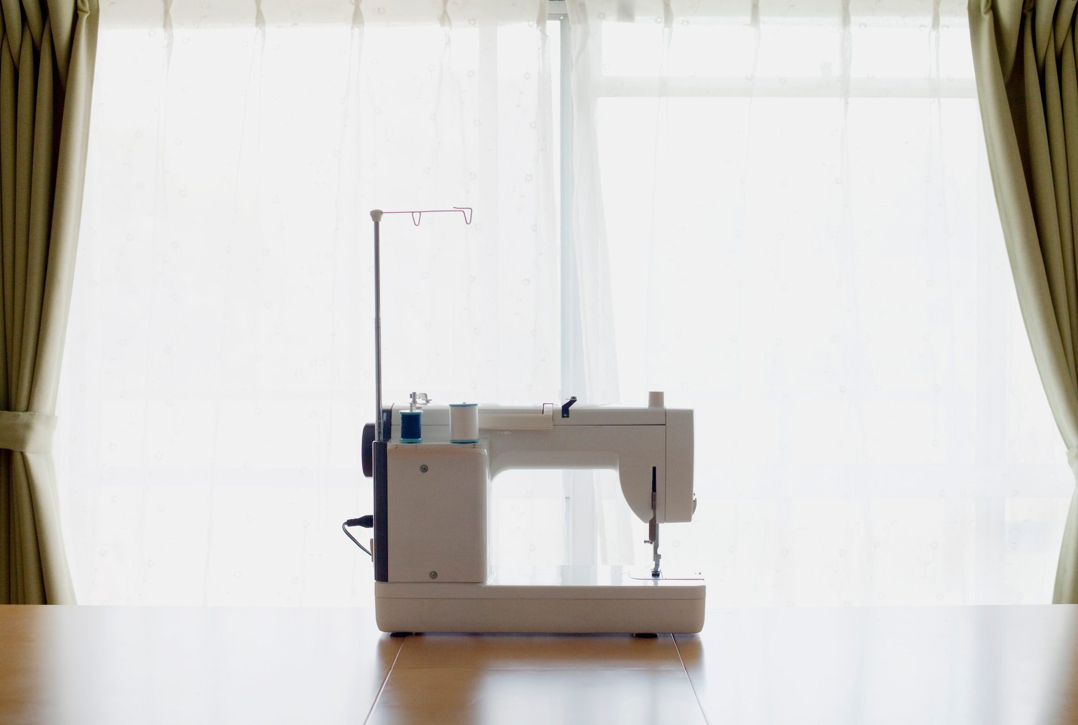 The white sewing machine on a desk.