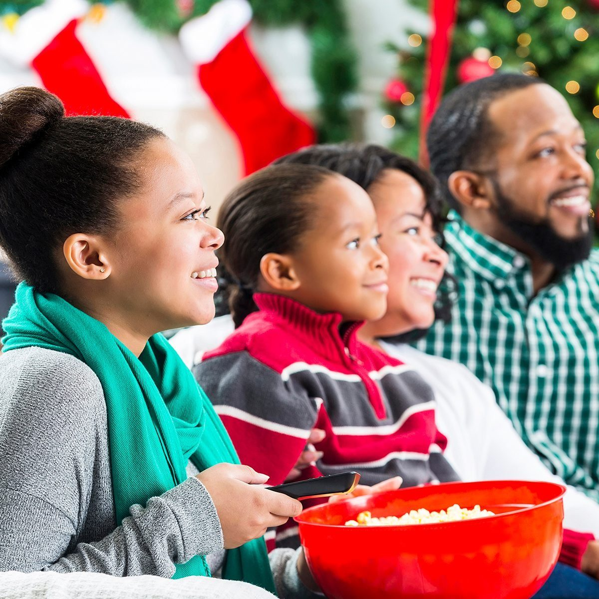 Happy African American couple and their teenage daughter and elementary age son watch a Christmas movie together during the Christmas season. The girl is holding a bowl of popcorn and the remote control. They are all smiling while watching the movie. A Christmas tree, stockings and a fireplace are in the background.