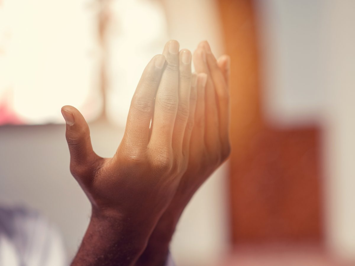 Hands of Muslim man praying with mosque interior background