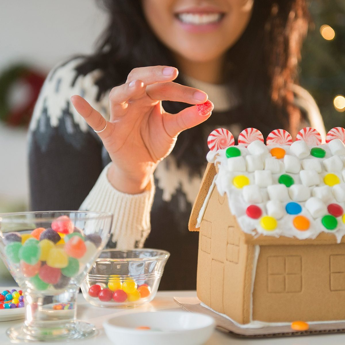 Pacific Islander woman decorating gingerbread house