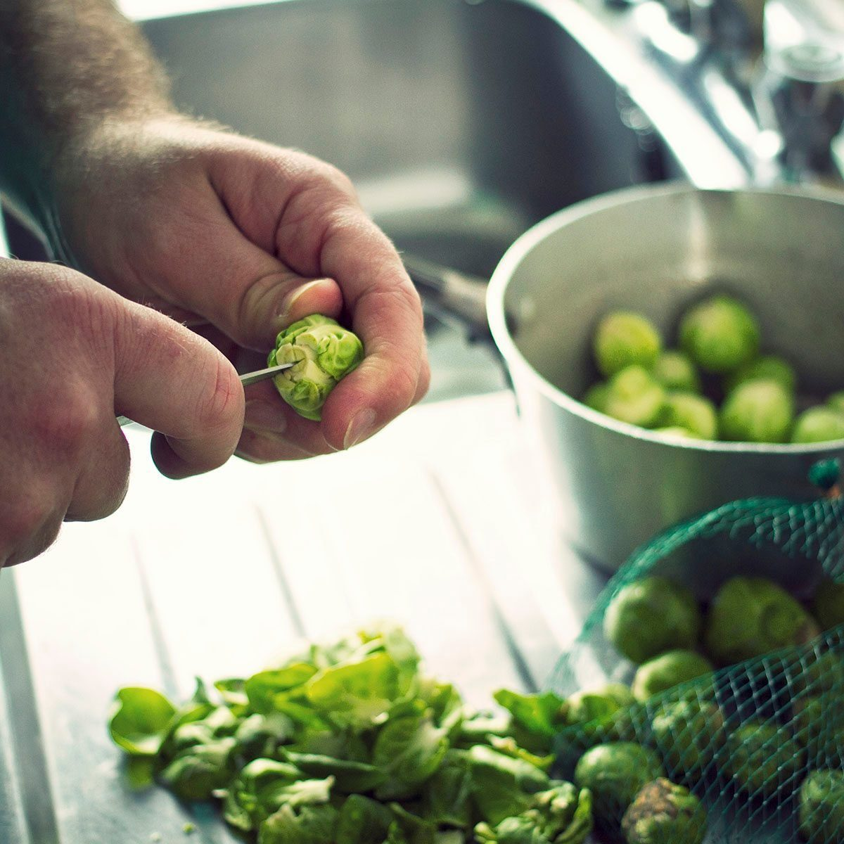Brussels Sprouts being prepared at a kitchen sink in readiness for Christmas Dinner