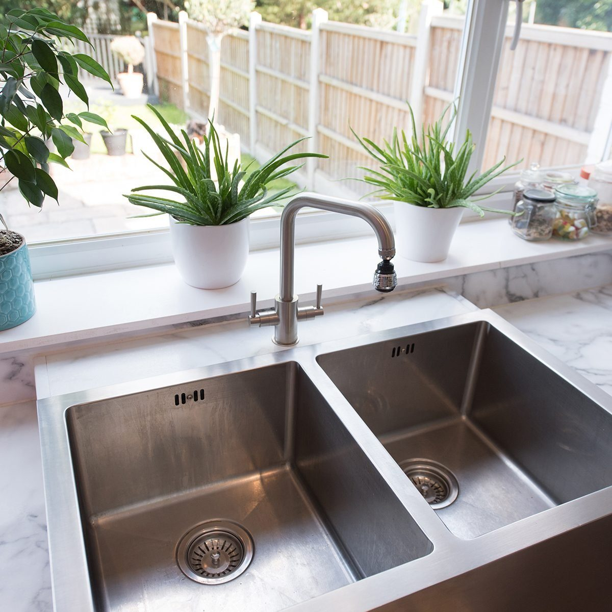A general view of a kitchen interior with a modern stainless steel twin sinks by a window with a view into the garden